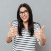 Picture of joyful young woman wearing eyeglasses make thumbs up gesture over grey background. Look at camera.
